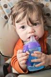 Bebé con la botella de Sippy Foto de archivo