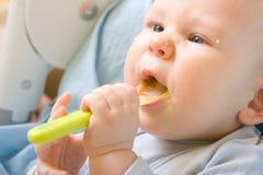 Bebé con la cuchara Fotos de archivo
