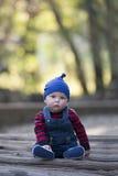 Bebé con la gorrita tejida en un día del otoño que brilla intensamente Imagen de archivo libre de regalías