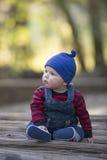 Bebé con la gorrita tejida en un día del otoño que brilla intensamente Fotografía de archivo