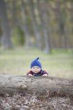 Bebé con la gorrita tejida en un día del otoño que brilla intensamente Imagen de archivo