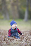 Bebé con la gorrita tejida en un día del otoño que brilla intensamente Foto de archivo libre de regalías