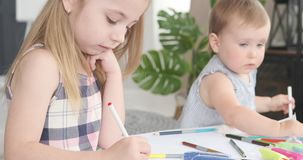 Bebé con la hermana que dibuja en el papel almacen de metraje de vídeo