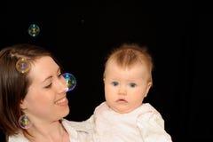Bebé con la madre Foto de archivo