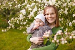 Bebé con la madre en el parque en los rayos de la puesta del sol Niño con la mamá en la naturaleza al aire libre Contraluz Escena fotografía de archivo