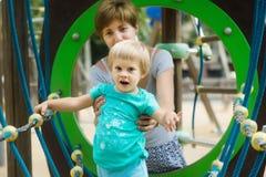 Bebé con la madre en el patio Imagenes de archivo