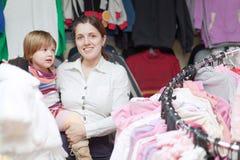 Bebé con la madre en la tienda de la ropa Fotografía de archivo