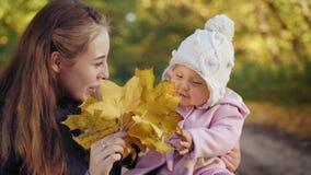 Bebé con la madre que sonríe en el parque del otoño metrajes