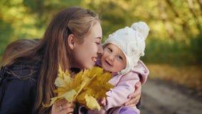 Bebé con la madre que sonríe en el parque del otoño almacen de metraje de vídeo