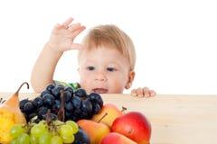 Bebé con la pila de fruta Imagenes de archivo