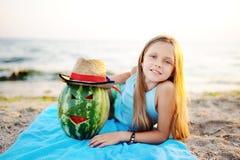 Bebé con la sandía que miente en la playa contra el mar Foto de archivo libre de regalías