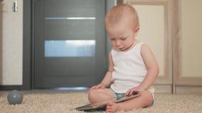 Bebé con la tableta que se sienta en el piso en casa, dentro Bebé hermoso del niño que juega con la pantalla almacen de metraje de vídeo