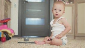 Bebé con la tableta que se sienta en el piso en casa, dentro Bebé hermoso del niño que juega con la pantalla metrajes