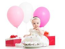 Bebé con la torta, los globos y los regalos Fotografía de archivo