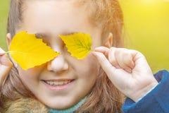 Bebé con las hojas de otoño foto de archivo