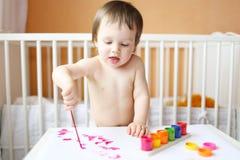 Bebé con las pinturas Imagen de archivo