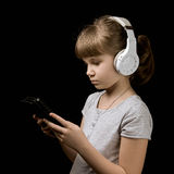 Bebé con los auriculares y el teléfono en fondo oscuro Imagen de archivo libre de regalías