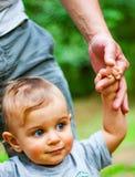 Bebé con los ojos azules en parque Confíe en las manos de la familia del hijo y del padre del niño fotos de archivo libres de regalías