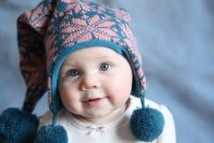 Bebé con los ojos azules en un casquillo del invierno Fotografía de archivo libre de regalías