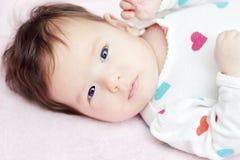 Bebé con los ojos azules que miran la cámara Imagen de archivo