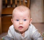 Bebé con los ojos azules que miran la cámara Fotos de archivo libres de regalías