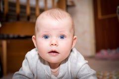 Bebé con los ojos azules que miran la cámara foto de archivo