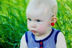 Bebé con los pendientes de la cereza Foto de archivo libre de regalías