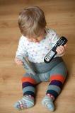 Bebé con mandos a distancia Fotografía de archivo