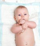 Bebé con mentiras y mirada de los ojos azules en la cámara Imagenes de archivo