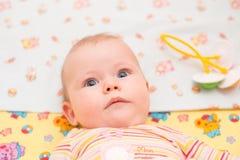 Bebé con mentiras y mirada de los ojos azules en la cámara Foto de archivo libre de regalías