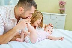 Bebé con risas sonrientes de la mamá y del papá en el cuarto fotografía de archivo libre de regalías