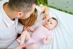 Bebé con su madre y padre en la cama que juega junto hap Foto de archivo libre de regalías