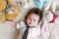 Bebé con sus peluches en una alfombra Foto de archivo libre de regalías