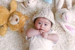 Bebé con sus peluches en una alfombra Fotos de archivo libres de regalías