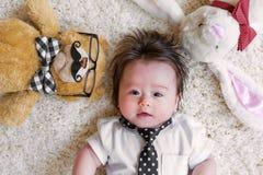 Bebé con sus peluches en una alfombra Imagenes de archivo