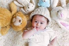Bebé con sus peluches en una alfombra Fotos de archivo