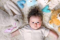 Bebé con sus peluches en una alfombra Foto de archivo