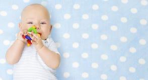 Bebé con Teether Toy In Mouth sobre muchacho infantil azul, feliz del niño en mono foto de archivo