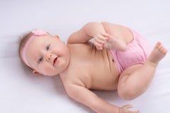 Bebé con un cubrepañal y una venda rosados Imagen de archivo