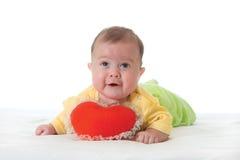 Bebé con un juguete suave bajo la forma de corazón imágenes de archivo libres de regalías
