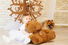 Bebé con un oso de peluche marrón suave en el interior con Chri Foto de archivo