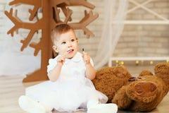 Bebé con un oso de peluche marrón suave en el interior con Chri Imagen de archivo