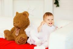 Bebé con un oso de peluche marrón suave en el interior con Chri Fotografía de archivo