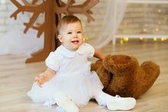 Bebé con un oso de peluche marrón suave en el interior con Chri Imagenes de archivo