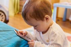 Bebé con un smartphone Fotografía de archivo