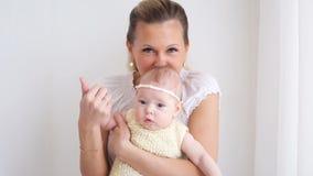 Bebé con una venda que se sienta en los brazos metrajes