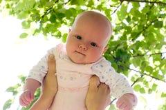 Bebé contra las hojas asoleadas Fotos de archivo libres de regalías