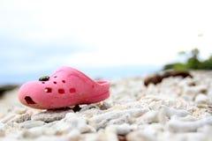 Bebé Crocs en la playa Imagenes de archivo