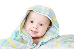 Bebé cubierto por una manta azul en un fondo blanco Foto de archivo libre de regalías