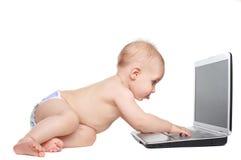 Bebé curioso con la computadora portátil Imágenes de archivo libres de regalías